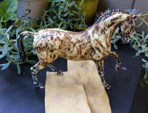 Do It Yourself of repainting Breyer model for home decor. Sanding old paint off model.