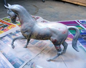 Do It Yourself of repainting Breyer model for home decor. Spraying light first layer.
