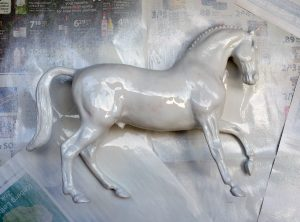Do It Yourself of repainting Breyer model for home decor. Spraying multiple layers.